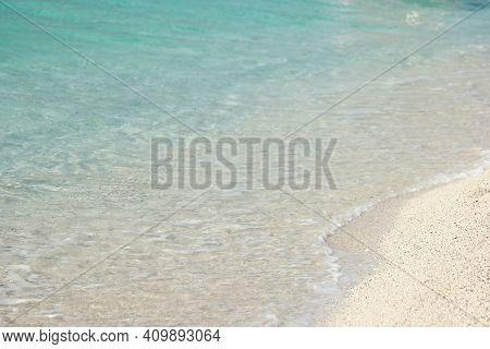Calm Sea Waves On Beautiful Sandy Beach. Close Up Of Blue Sea Water Waves On White Sandy Beach. Vaca