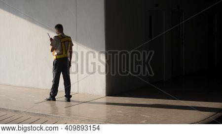 Asian Security Guard In Safety Vest Walking On Sidewalk Of Parking Garage, He Using Walkie-talkie Or