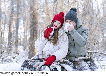 Young Couple In Love In Winter Park Drinks Tea And Wrapped Themselves In Blanket. Love Story Photosh