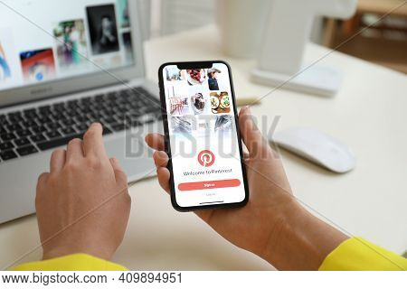 Mykolaiv, Ukraine - August 28, 2020: Woman Holding Iphone 11 With Pinterest App On Screen At Table,