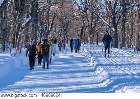 Montreal, Ca - 4 February 2021: People Walking Or Skiing On A Snowy Trail In Montreal's Mount Royal