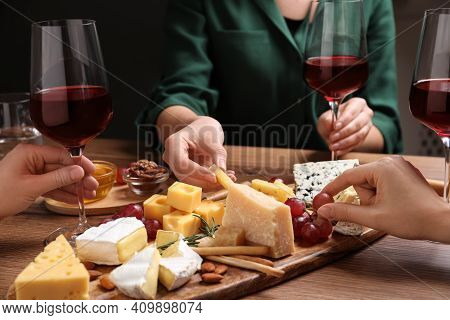 Women With Cheese Plate And Glasses Of Wine At Wooden Table, Closeup