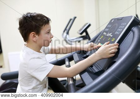 Boy Exercising At Stride Treadmill