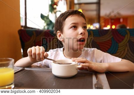 Boy Has Breakfast In Restaurant