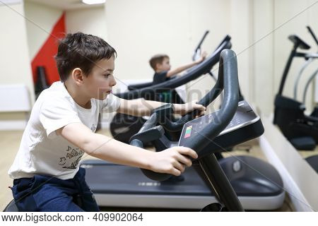 Child Exercising On Stationary Bike In Gym