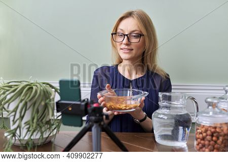 Activation Of Vitamins And Minerals In Nuts. Woman Nutritionist Soaking Nuts In Water, Consulting On