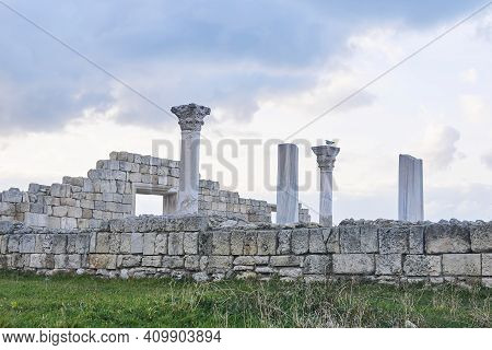 Ruins Of An Ancient Greek Temple With Columns Against A Winter Cloudy Sky