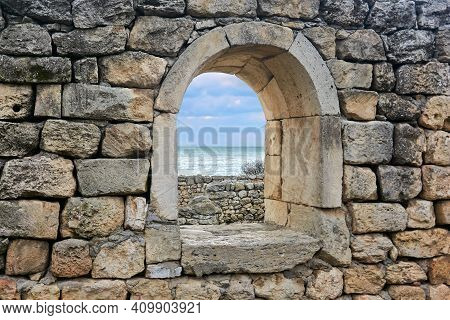 Semicircular Window Opening In The Ruins Of An Antique Wall, Behind Which You Can See The Sea