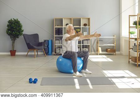 Elderly Man Sitting And Exercising On Fitness Ball With Arms Stretched At Home Or In Rehabilitation
