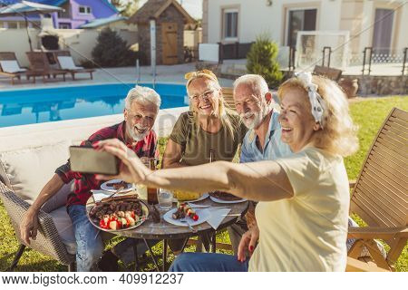 Group Of Elderly Friends Taking A Selfie While Having Lunch In The Backyard By The Pool, Gathered Ar