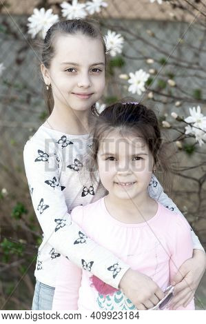 Little Girls Pose On Floral Blossom In Spring Garden. Sisters Enjoy Spring Day Outdoor. Children Wit