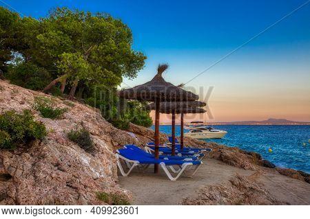 Beach umbrellas at rocks beach in sunset time. Mallorca island, Spain Mediterranean Sea, Balearic Islands.