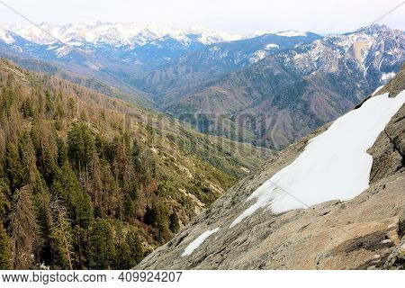 Snow On A Granite Rock Dome Which Was Shaped From Past Glaciers Overlooking An Alpine Coniferous For