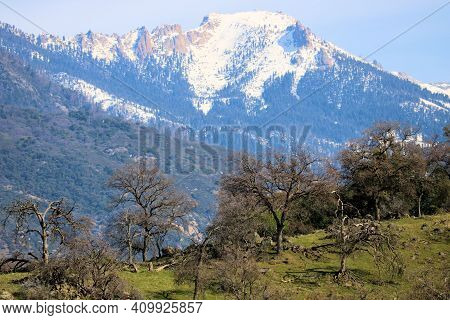 Rugged Snow Capped Peaks Taken From The Lush Green Grasslands In The Foothills Of The Sierra Nevada