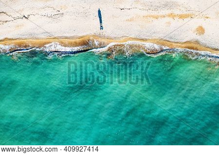 Aerial Top View Of Single Human Figure Casting Shadow On Sandy Beach, Standing By Sea With Beautiful
