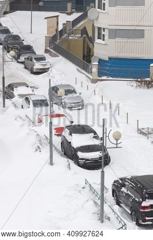 Moscow / Russia - February 13 2021: Cars In Street Parking Near Apartment Building Under Thick Layer