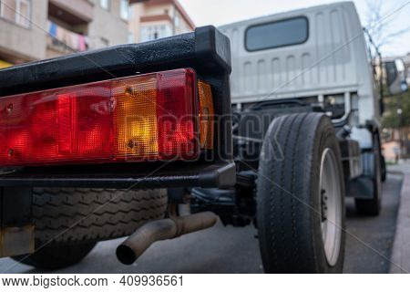 Rear View Of Small Lorry Delivery Mini Cargo Truck And Back Light In City Low Angle
