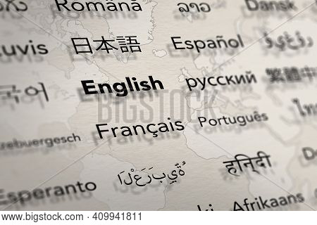 Several Important Languages On Paper With World Map Background. Depth Of Field Image. Translate And
