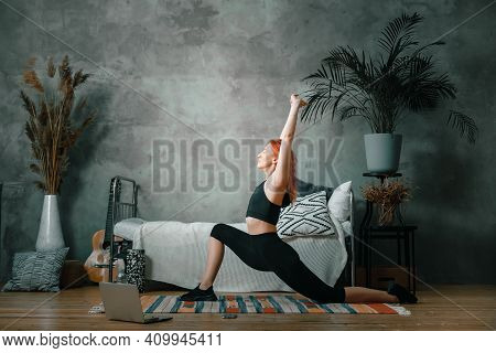 A Young Woman Goes In For Sports At Home, Online Workout . The Athlete  Stretching , Meditating, Sit