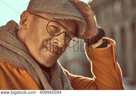 Close up portrait of a handsome mature man in elegant clothes and glasses walking on a city street. Optics style. Fashion for men.