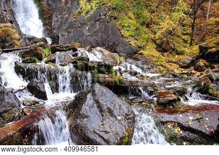 A Small Stream Flows Down From The Mountain, Bending Around The Fallen Trees And Large Stone Boulder