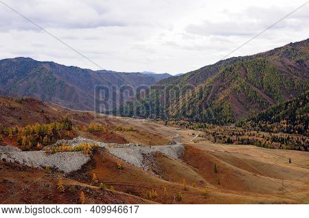 The Mountain Road Serpentine Descends From The Cliff Into A Picturesque Autumn Valley.
