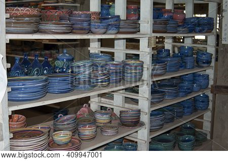 Shelves Of Artisan Pottery In Countryside Pottery Store.