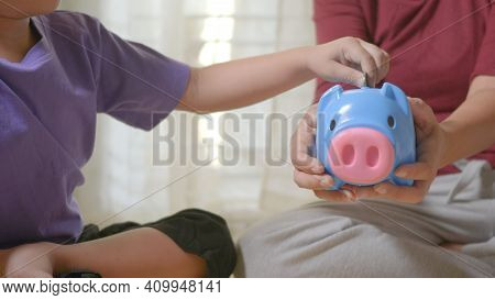 Happy Asian Kid Boy Preschool And Mother Putting Pin Money Coins Into Piglet. Little Child Putting C