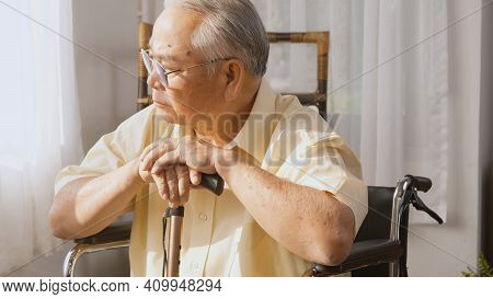 Pensive Disabled Elderly Patient Sit On Wheelchair Alone, Sad And Depressed Lonely Asian Senior Old