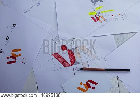 Sketches And Drawings Of The Logo Printed On Paper. Development Of Logo Design In The Studio On A Ta