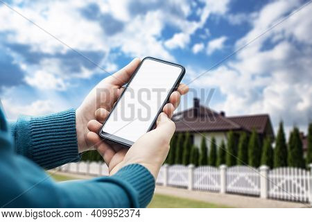 Man Holds A Smartphone With A White Screen In His Hands Close-up Against The Backdrop Of A House Wit