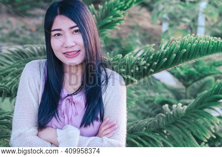 Portrait Of Asian Happy Woman Smiling With Pine (araucaria Heterophylla) Green Leaves Background.