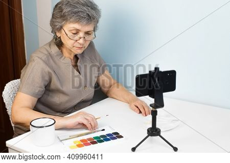 Senior Woman With Glasses Painting A Watercolor Picture At Home. Pensioner Taking An Online Drawing