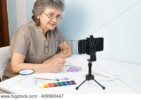 Senior Woman Taking A Painting Course Online. An Elderly Woman In Glasses Paints Flowers With Waterc