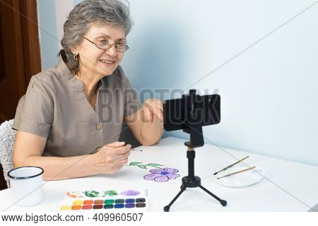 Smiling Senior Woman Taking Painting Course Online. An Elderly Woman In Glasses Paints Flowers With