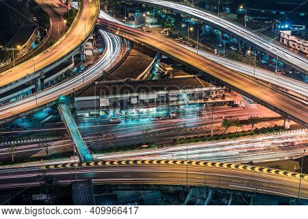 Aerial View Of The Modern Buildings And Highway At Night Of Bangkok City, Thailand. Car Lights In Ev