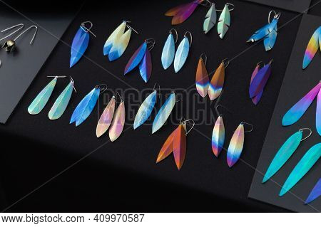 Assortment Of Earrings With Colorful Titanium Oxide Patterns Lay On A Black Background