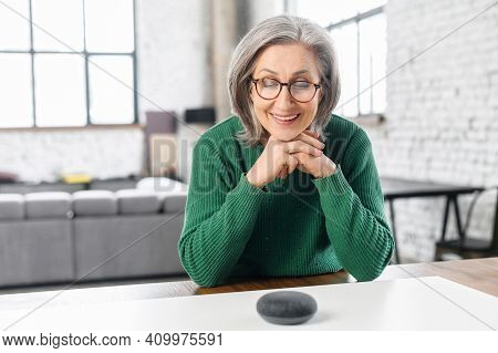 Modern Granny Smiling And Saying, With Elegant Glasses, Loft Style Apartment, Rests Her Chin On The