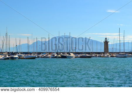 Lake Landscape With Sailboats, Lighthouse, Blue Water, White Clouds, Mountains In Haze. Lake Garda I