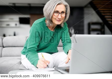 Lively Aged Woman Grey Haired Busy As A Bee, Stylishly Dressed, Sitting At The Laptop, Loft Style Ap