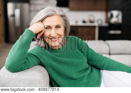Smiling Elderly Woman With Grey Well-groomed Hair, Blue Eyes And Beautiful Wrinkles, Sitting On The