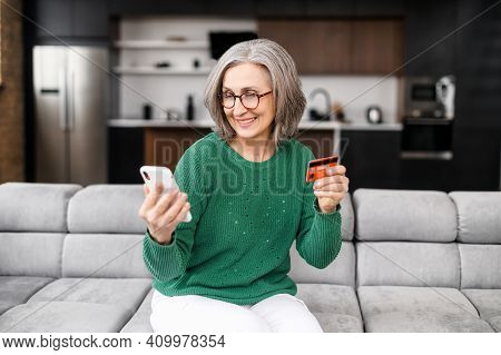 Well-dressed Gray Haired Woman On Retirement Managing Family Budget At Home, Smile And Paying The Bi