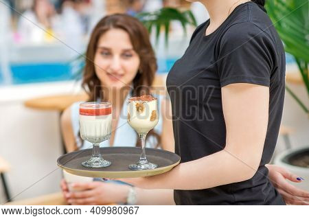 A Young Waitress Carrying A Tray With Two Different Desserts In A Two Glass On The Background Of A Y