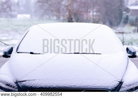 A Portrait Of A Car Starting To Get Snowed Under During A Snowstorm. The Snow Already Covers The Win