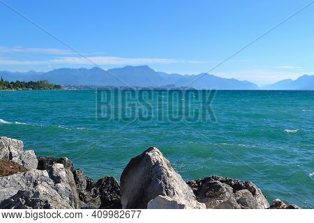 Lake Garda In Italy. Blue Water, White Clouds, Mountains In Haze. Vacation Concept