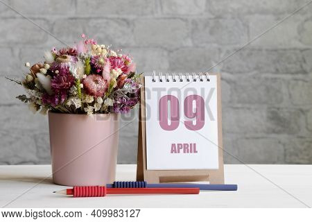 April 09. 09-th Day Of The Month, Calendar Date.a Delicate Bouquet Of Flowers In A Pink Vase, Two Pe