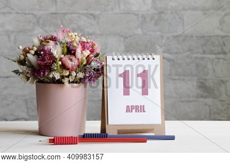 April 11. 11-th Day Of The Month, Calendar Date.a Delicate Bouquet Of Flowers In A Pink Vase, Two Pe