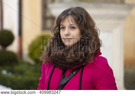 European Young Woman 30-35 Years Old With Dark Curly Hair Against The Backdrop Of A City Landscape W