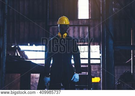 Portrait Worker Man With Yellow Helmet And Ear Protection In Factory, Dark Tone