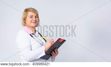 Banner- Long Format. An Attractive Senior Female Doctor In White Coat With Sthetoscope, Writes Analy